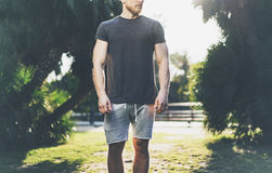 Photo Bearded Muscular Man Wearing Black Empty t-shirt and shorts in summer holiday.Walking Green City Garden Park. Background. Front view. Horizontal Mockup Royalty Free Stock Photography