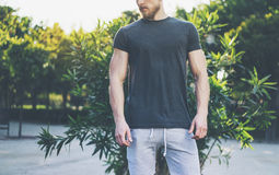 Photo Bearded Muscular Man Wearing Black Empty t-shirt and shorts in summer vacation. Relaxing time near the lake. Green. City Garden Park Sunset Background Stock Photography