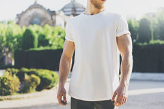 Photo Bearded Muscular Man Wearing White Blank t-shirt. in summer time. Green City Garden Background at sunset Royalty Free Stock Photos