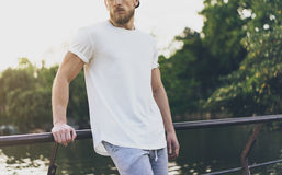 Photo Bearded Muscular Man Wearing White Empty t-shirt, snapback cap and shorts in summer holiday. Relaxing time near Stock Images