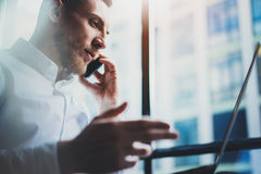Photo bearded young businessman working on modern office. Man wearing white shirt and using contemporary smartphone. Panoramic windows background. Horizontal Stock Photography