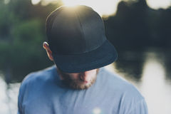Photo Bearded Young Man Wearing Black Blank Cap. Green City Park Lake Background and Sunset effect. Front view. Horizontal Mockup Stock Photo