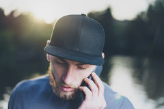 Photo Bearded Young Man Wearing Black Blank Cap Using Modern Smartphone. Green City Park Lake Background and Sunset. Effect. Front view. Horizontal Mockup Stock Photography