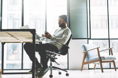 Photo bearded young man working with new project modern open space loft. Using contemprary mobile phone hands. Creative Royalty Free Stock Images