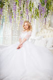 Photo of a beautiful blonde bride in a luxurious wedding dress in interior Royalty Free Stock Photography