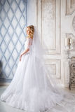 Photo of a beautiful blonde bride in a luxurious wedding dress in interior Royalty Free Stock Photos