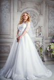 Photo of a beautiful blonde bride in a luxurious wedding dress in interior. Photo of a beautiful blonde bride in a luxurious wedding dress in elegant expensive Stock Photo