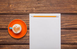 Photo of beautiful blue cup of coffee and sheet of paper with pe Stock Photo