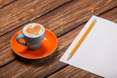 Photo of beautiful blue cup of coffee and sheet of paper with pe Stock Image