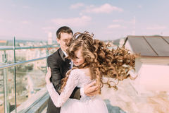 Photo of beautiful bride and groom dancing on roof top at sunny day Stock Images