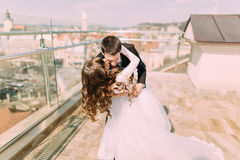Photo of beautiful bride and groom dancing on roof top at sunny day Stock Photos