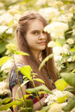 Photo of beautiful brunette girl posing at flowering bushes Royalty Free Stock Photos
