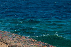 Photo of beautiful clear turquoise sea ocean water surface with ripples and bright splash on stone seascape background Royalty Free Stock Photo