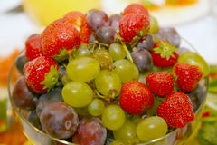 Photo of beautiful and delicious fruits and berries, grapes, strawberries and plums lying heaped in a round glass vase. Stock Image