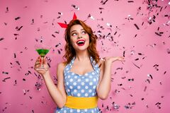 Photo of beautiful excited lady hold green cocktail theme retro party enjoy confetti falling prom queen wear red