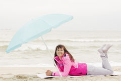 Photo of beautiful girl in a coat lying on a sandy beach Stock Photos