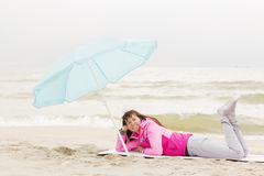 Photo of beautiful girl in a coat lying on a sandy beach Royalty Free Stock Image