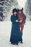 Photo of a beautiful girl in full growth in black coat, horse, w Stock Photography