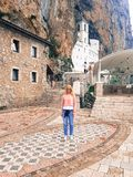 Beautiful Girl stands at the entrance to the old Orthodox Monastery. This is photo of Beautiful Girl who stands at the entrance to the old Orthodox Monastery in royalty free stock image