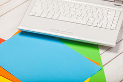 Photo of beautiful laptop and colorful sheets of paper on the wo Stock Photography