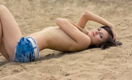 Photo of a beautiful model relaxing on a beach Stock Images