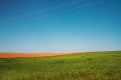 Beautiful rural landscape with  on a green and  brown plowed field on a background of blue sky Royalty Free Stock Photography