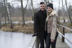 A photo of a beautiful Scandinavian young couple standing on bridge in Swedish winter landscape. Royalty Free Stock Image