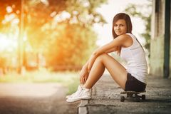 Beautiful skater girl in summer city. Photo of Beautiful skater girl in summer city royalty free stock photography