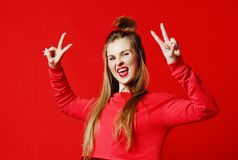 Photo of beautiful, smiling, positive girl showing peace symbol, looking at camera, posing on colorful background. stock photos