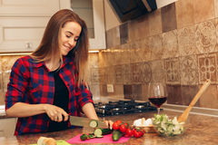 Photo of beautiful smiling woman making a salad. In the kitchen Royalty Free Stock Photos