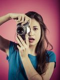 Beautiful brunette pointing vintage camera. Photo of a beautiful woman pointing a vintage camera with a surprised look on her face Royalty Free Stock Photos