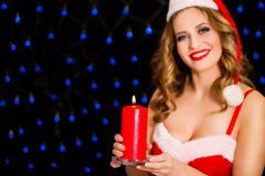 Beautiful woman in Santa dress with candle. Photo of Beautiful woman in Santa dress with candle Stock Photos