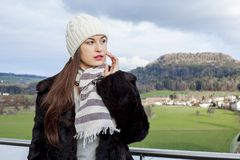 Beautiful woman outside in the cold weather. Photo of a beautiful woman standing outside in the cold weather wearing a hat, scarf, and coat royalty free stock photos