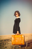 Photo of beautiful young girl standing with suitcase in the fiel Royalty Free Stock Image