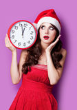 Photo of beautiful young woman with clock in santa claus hat on Royalty Free Stock Image