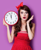 Photo of beautiful young woman with clock on the wonderful purpl Royalty Free Stock Images