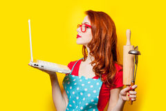 Photo of beautiful young woman with cooking equipment and laptop Stock Images