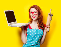 Photo of beautiful young woman with cooking equipment and laptop Royalty Free Stock Images