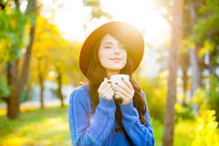 Photo of beautiful young woman with cup of coffee standing in th Stock Photography