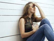 Gorgeous brunette woman drinking coffee. Photo of a beautiful young woman drinking coffee leaning up against a wood wall stock image