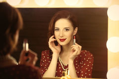 Photo of beautiful young woman holding her lipstick near the win Royalty Free Stock Image