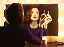 Photo of beautiful young woman holding her lipstick near the win royalty free stock images