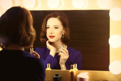 Photo of beautiful young woman holding her lipstick near the win stock image