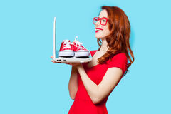 Photo of beautiful young woman holding laptop with gumshoes on i. T on the wonderful blue studio background royalty free stock photos
