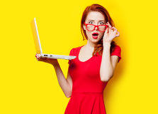 Photo of beautiful young woman holding laptop on the wonderful y. Ellow studio background stock photography