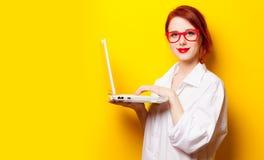 Photo of beautiful young woman holding laptop on the wonderful. Yellow studio background stock photo