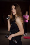 Photo of beautiful young woman with long hair and dumbbells at the gym stock images
