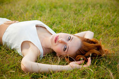 Photo of beautiful young woman lying in the field and relaxing. Beautiful young woman lying in the field and relaxing Royalty Free Stock Photos