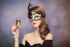 Photo of beautiful young woman in mask with wineglass of champagne on the wonderful black studio background stock photography