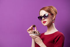 Photo of beautiful young woman with plate full of chocolate cand Royalty Free Stock Photography